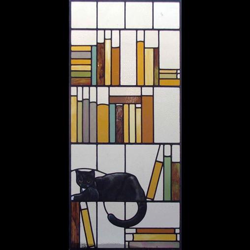 Stained glass panel with cat and bookshelf design